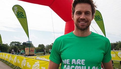 Celebrity Andrew Cooper smiles at a Macmillan outdoor event.
