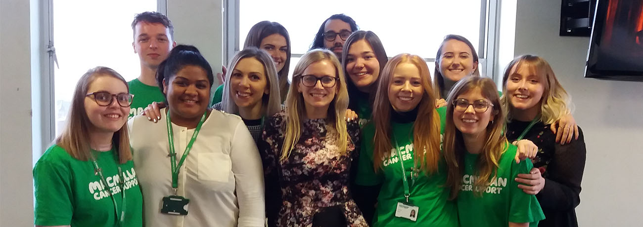 A group of Macmillan interns stand smiling in an office room.