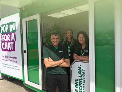 Three Macmillan staff stand in the doorway of the Basil information and support bus
