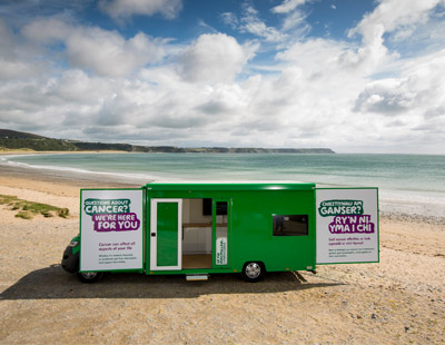 The Bronwen information and support bus parked on a beach with cliffs and sea in the background.