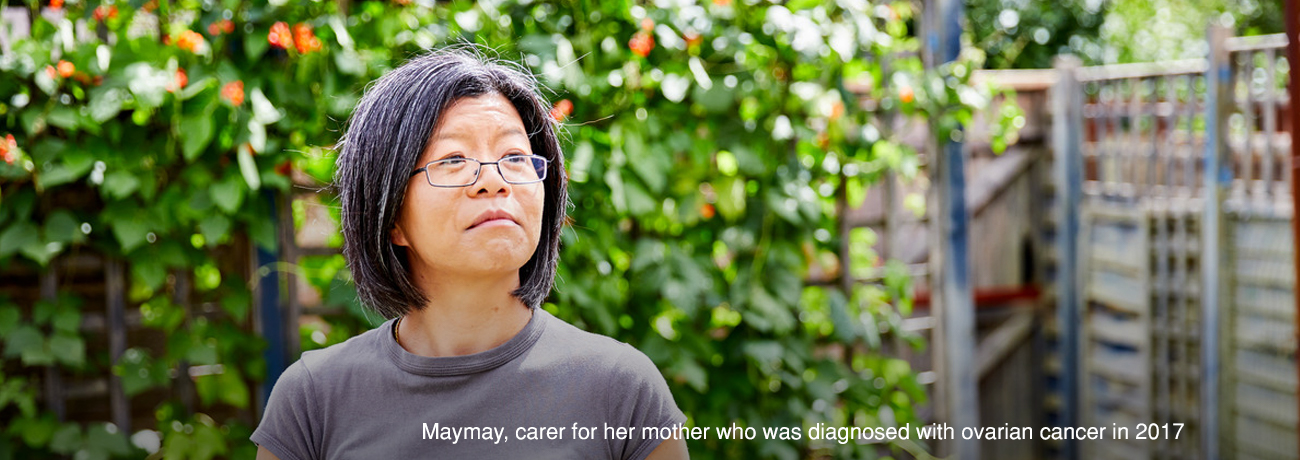 A woman stands in her garden looking away from the camera. The caption reads, 'Maymay, carer for her mother who was diagnosed with ovarian cancer in 2017'.