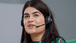 A woman wearing a call headset - on the phone