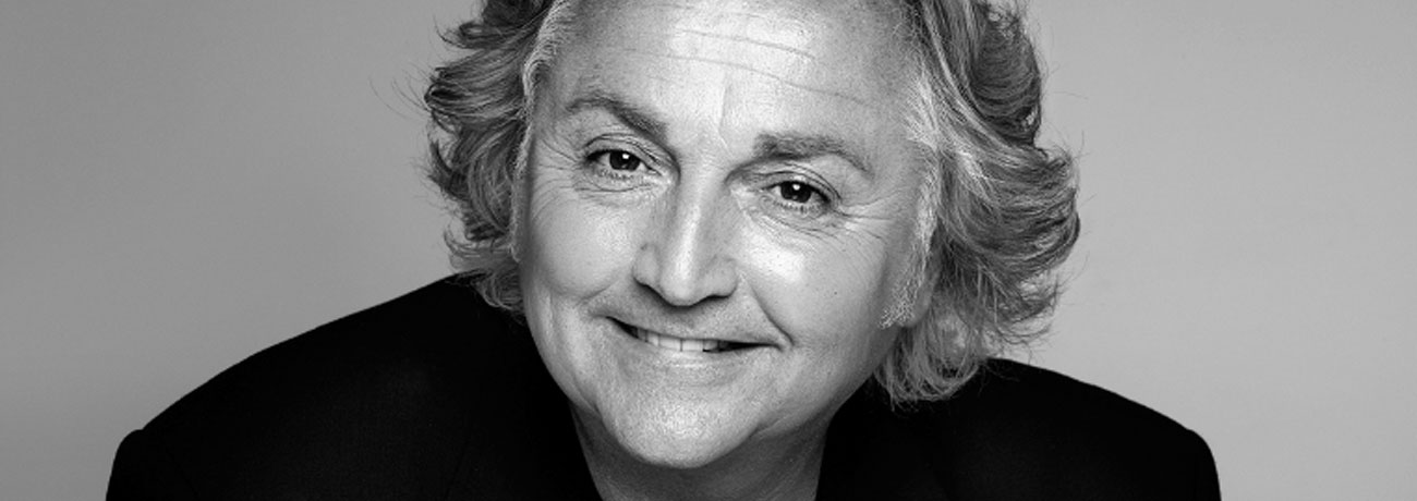 Celebrity fashion designer David Emanuel smiling.