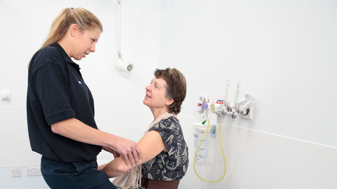 Physio Clare examines Diane's arm in a treatment room.