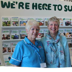 Supporters smiling standing in a cancer information centre in the East Midlands.
