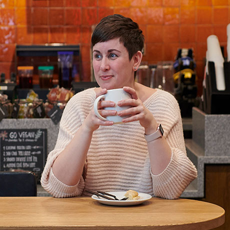 A woman with short cropped dark hair sitting in a café. She is holding a white mug with both hands.