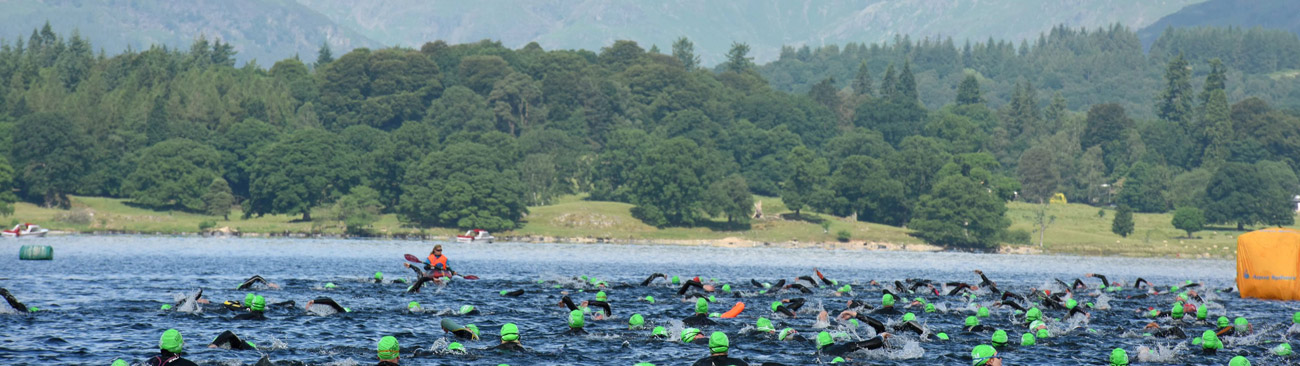 A large group of swimmers wearing green swimming caps and wetsuits, swimming across a giant lake.