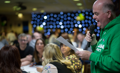 A man in a green Macmillan hoodie, asking questions through a microhone to a room full of people sat around tables.