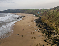 Giant footprints appear on the sand of Cayton Bay beach to represent 50,000 cancer patients missing diagnoses.