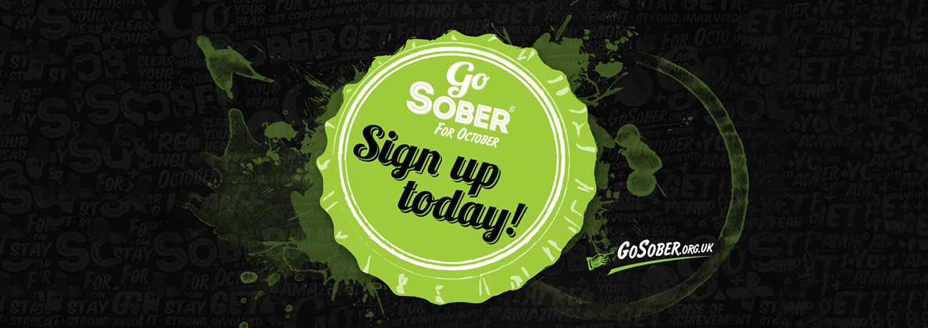 A large green bottle top against a black background, with the words 'Go Sober for October' on.
