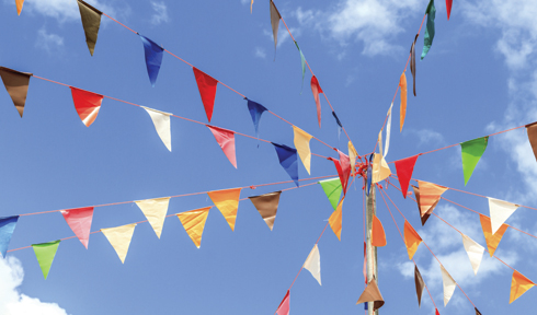 An assorted range of multicoloured flags hanging across a blue sky.