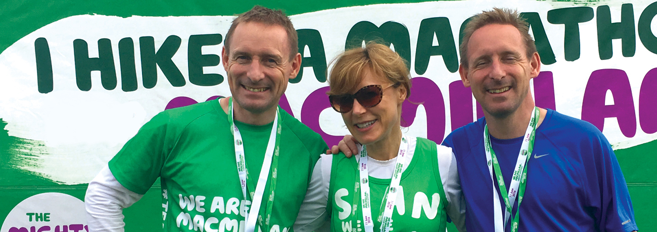A middle aged woman in a Macmillan running vest, standing in between two middle aged men also in running attire. They have all just finished a race and are posing together with their medals around their necks.