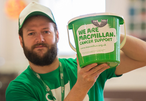 A white bearded man wearing a green Macmillan tshirt and cap, holding up a green Macmillan collection bucket. His name is Jonjo.