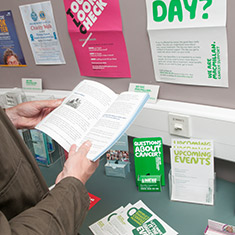 A man's hands holding an information booklet in front of a table of other cancer information resources.