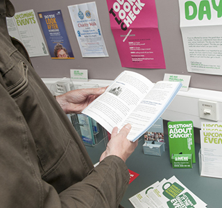Someone holding open a Macmillan information leaflet and reading the contents.