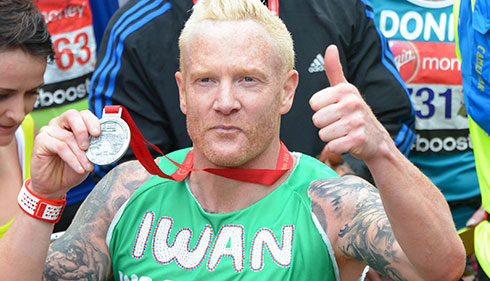 Celebrity Iwan Thomas holds up his medal.