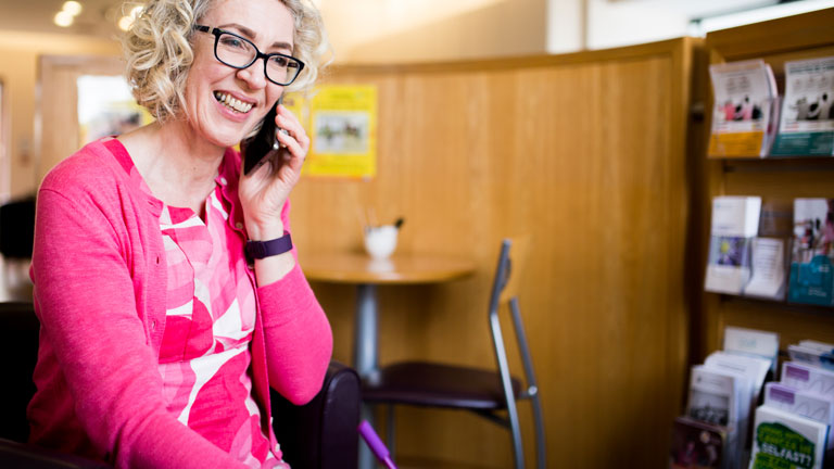 Joanne talking on the phone. She is wearing a pink jacket and has curly blonde hair.