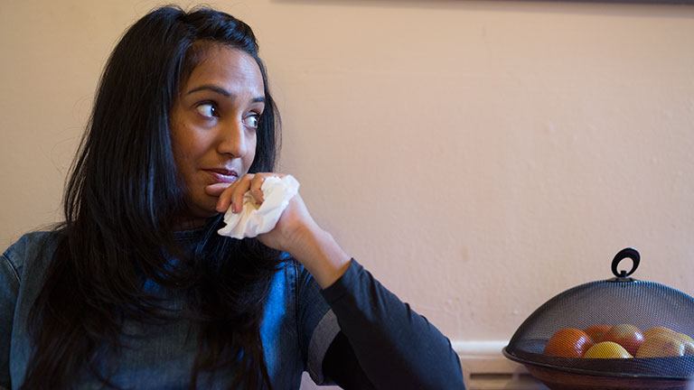 Kiran sitting in her kitchen, holding a tissue.