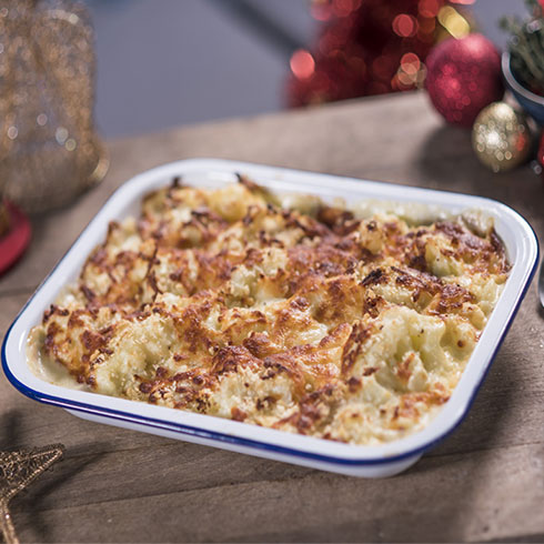 A creamy leek and cauliflower bake surrounded by Christmas decorations.