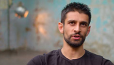 Close-up of Amuz, a young man with dark hair and beard, sits in a stripped back room and talks to the camera.