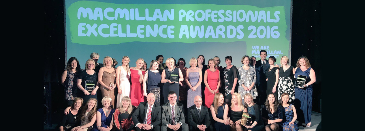 A group of Macmillan Professional award winners stand on stage with Gethin Jones.