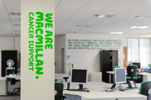 Internal view of Macmillan office with computers and desk in the background the the words 'We are Macmillan. Cancer support' on the pillar in the foreground.
