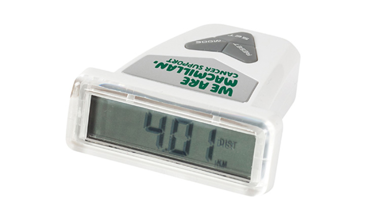 A photograph of a white pedometer with the green Macmillan logo.
