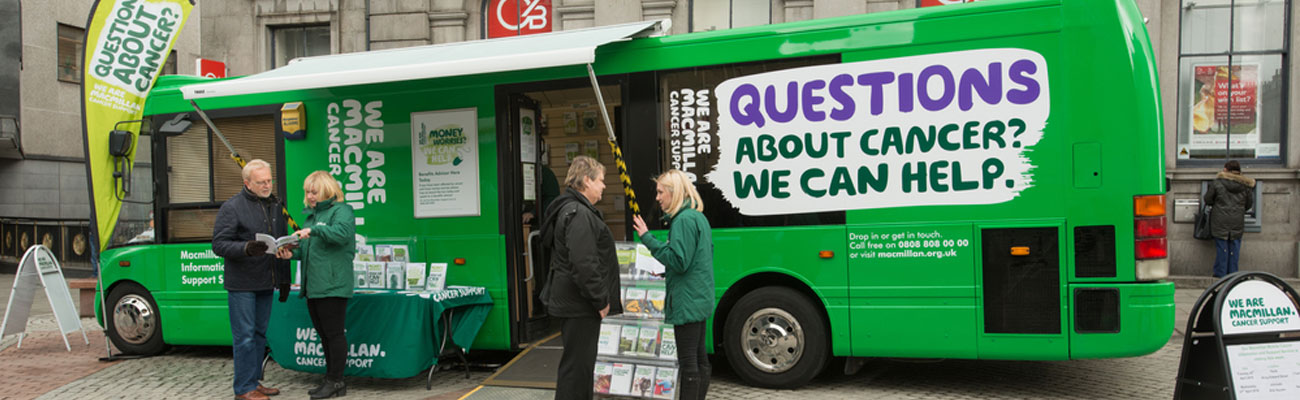 One of Macmillan's information and support buses in a street with two Macmillan staff members talking to members of the public.