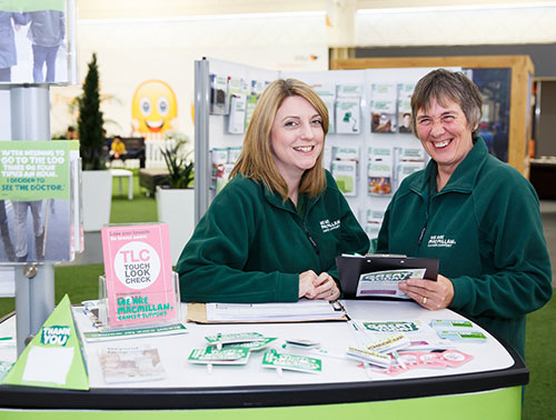 A Macmillan staff member sits at an information stand in Boots, there are lots of leaflets and cancer information booklets on the table.
