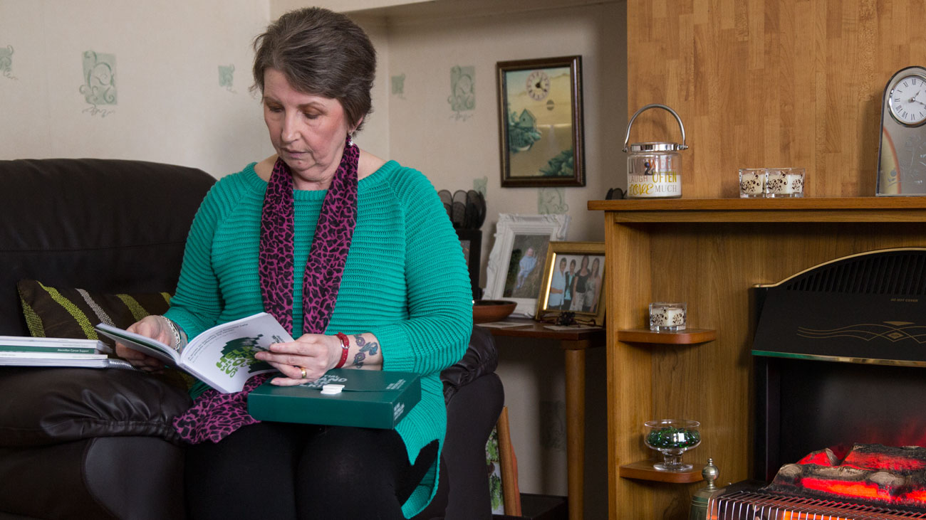 Cath reads a Macmillan booklet. She is seated in a chair in her home.