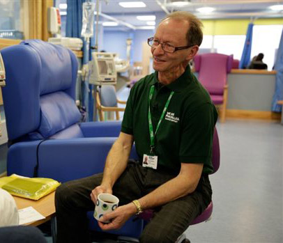 Murray sits in a hospital ward holding a cup of tea