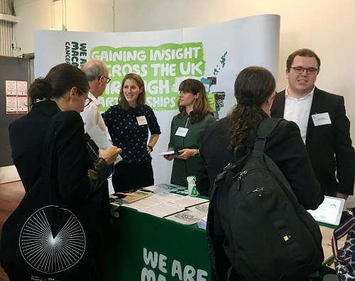 Macmillan evidence staff stand behind a Macmillan-branded stall with leaflets and speak to conference attendees.