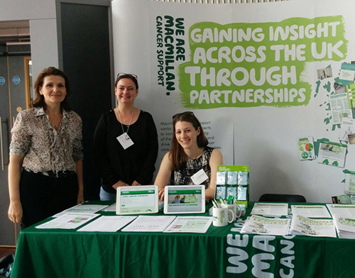 Three staff members stand by the Macmillan stand at the Cancer data and outcomes conference 2017
