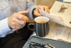 A man turning the page of a newspaper, a cup of coffee by his side.