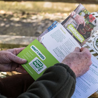 Hands holding a Macmillan Move More pack with a gardening leaflet inside.