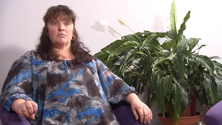 Video still shows Nikki, a middle-aged woman with shoulder length hair wearing a bold print dress. Nikki, from Ceredigion, talks about struggling with costs after her husband Ian was diagnosed with oesophageal cancer.
