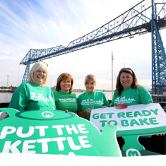 Supporters wearing green tshirts and holding placards 'get ready to bake', smiling beneath the Transporter Bridge in Middlesbrough.