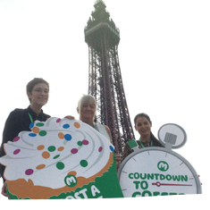 Supporters standing in front of Blackpool Tower holding cake shaped placards.