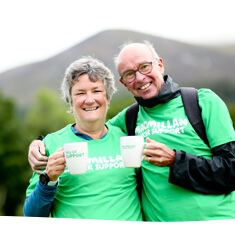 Man and woman in green Macmillan t shirts, holding Macmillan coffee mugs outside with a large hill in the background