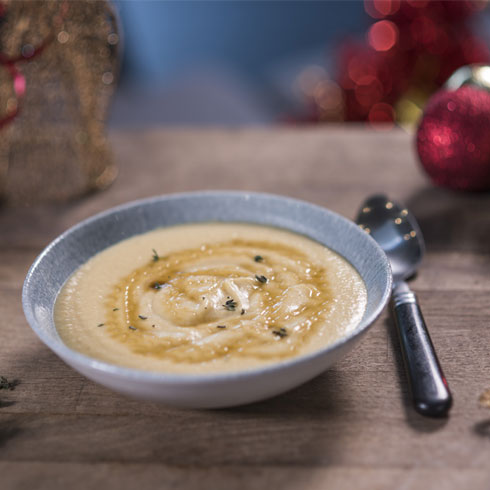 Parsnip soup in a bowl surrounded by Christmas decorations.