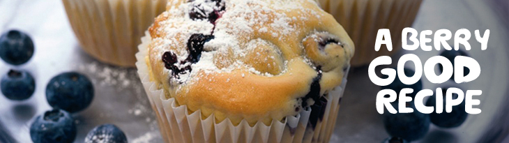 Close up of a blueberry muffin and a couple scattered blueberries, with the words 'A berry good recipe'.