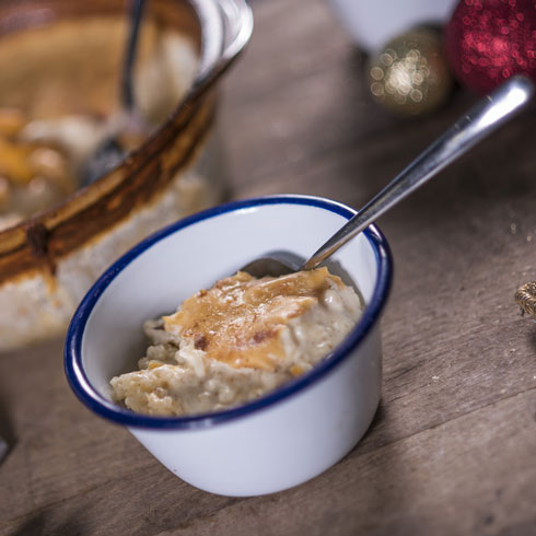 Rice pudding in a bowl surrounded by Christmas decorations.