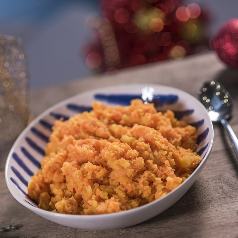 A plate of root vegetable mash on a plate, surrounded by Christmas decorations.