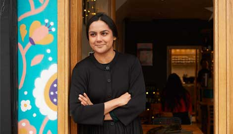 A woman, Saima, leans against the doorway of her restaurant