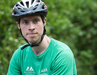 A young man wearing a bicycle helmet and a green T-shirt.