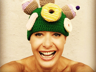 A woman wearing a knitted hat with donuts on it.