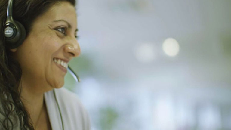 A woman called Maria smiles. She is wearing a telephone headset.