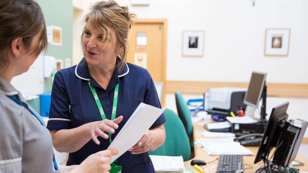 Shez, a Macmillan professional, is talking to another nurse. They are in discussion.