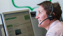 A profile of a Macmillan employee who is wearing a telephone headset, and facing a computer screen with the screen on a chemotherapy webpage.