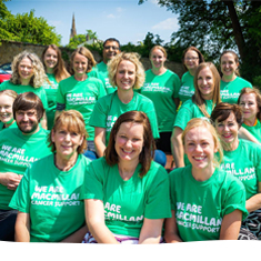 Supporters smiling, wearing green Macmillan t-shirts.